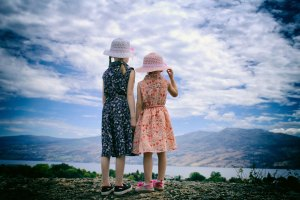 Two girls looking across a lake at a mountain