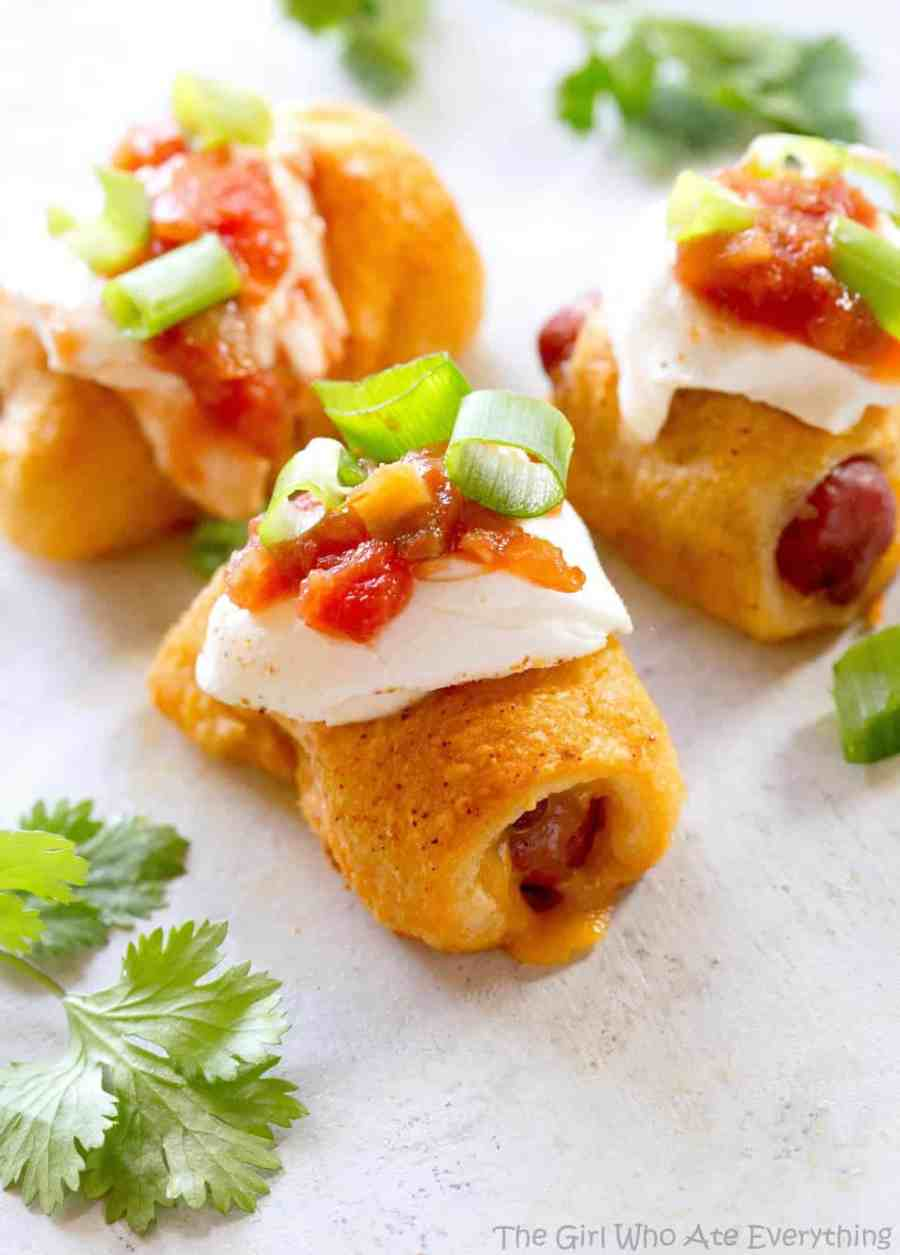Taco Pigs in a Blanket - a Mexican twist on the classic appetizer. Make a toppings bar so everyone can top their own. the-girl-who-ate-everything.com