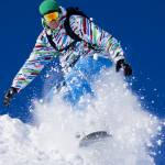 Snowboarder explodes through the fresh powder snow.