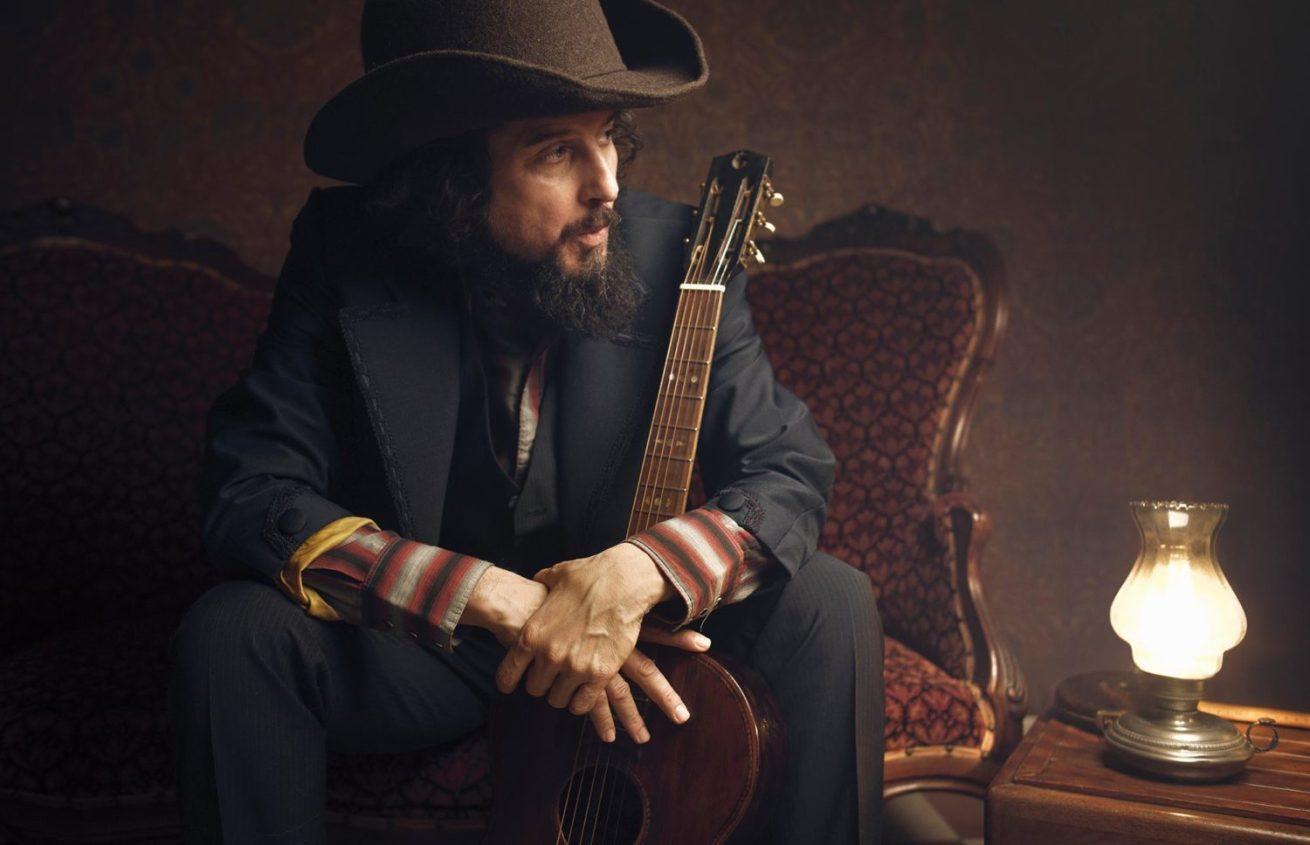 Vinicio Capossela seduto su una poltrona con la chitarra fra le braccia e luce morbida da una lampada
