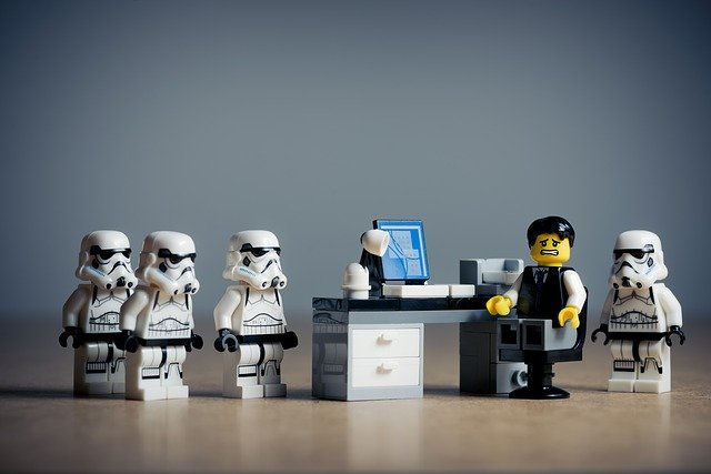 Lego man looking scared at desk with computer surrounded by four Lego Stormtroppers.