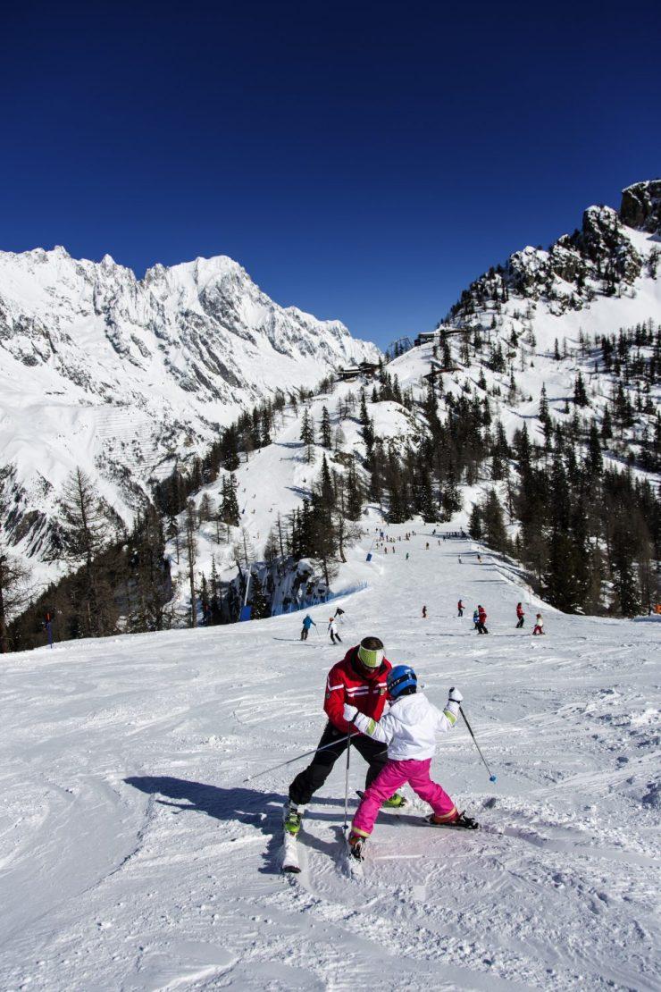 A ski instructor teaches a kid how to ski in Courmayeur