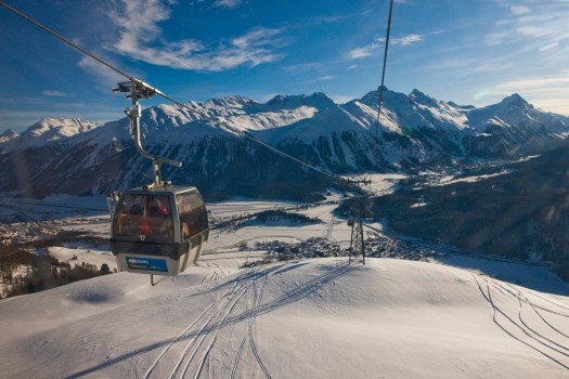 ENGADIN ST. MORITZ - View of the cable car operating between Celerina and Marguns. At the foot of the ski area, the village of Celerina; behind it, the snow-capped mountains and the village of Pontresina. Copyright by ENGADIN St. Moritz By-line:swiss-image.ch/Daniel Martinek