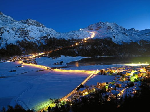 ENGADIN ST. MORITZ - Snow-night at Corvatsch - View from Silvaplana towards the longest illuminated ski slope of Switzerland (4.1 km). The illuminated slope begins at the middle station of Corvatsch and goes along the tree notch of the Surlej slope down to the station at the bottom which is just above the houses of Surlej. In the foreground the lights of the village of Silvaplana. Copyright by ENGADIN St. Moritz By-line:swiss-image.ch/Robert Boesch
