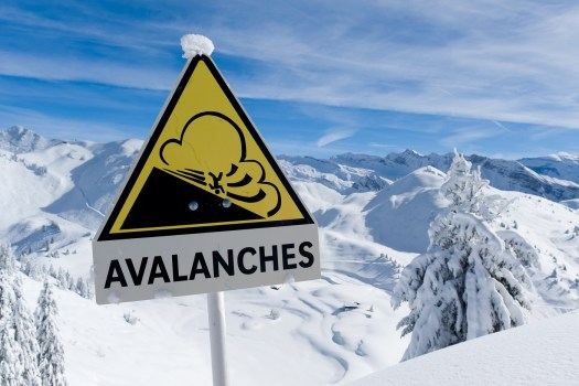 Avalanche sign in winter Alps with snow. One dead and three missing in the Verbier area.