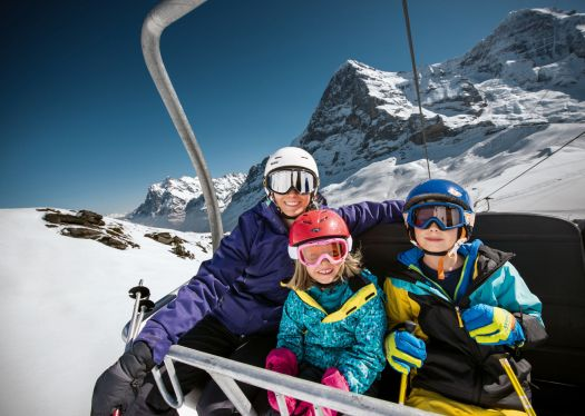 A family in a lift with the Eiger and Mönch to look at. Photo: Jungfrau Region. Over 1 Million Skier Visits for the Jungfrau Ski Region.