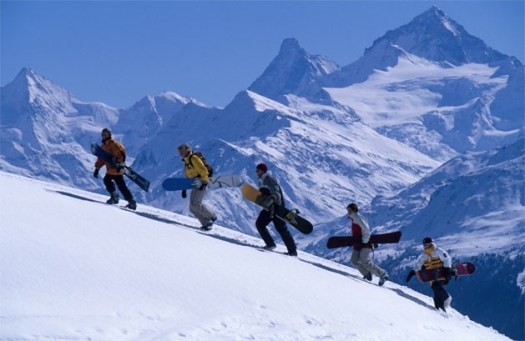A group of boarders hiking up for getting a grand descent down the slopes of Crans-Montana.