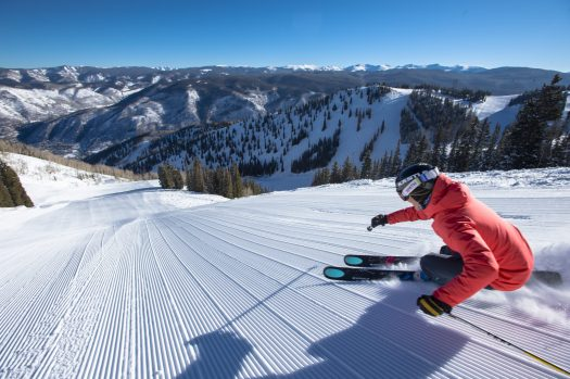 Darcy Conover skiing fresh corduroy down a steep snow covered groomed slope in the mountains at Aspen Mountain Ski Resort in Colorado - Alterra expects to sell 250,000 Ikon ski passes while Vail Resorts Epic Pass sales are up thanks to the $99 military pass