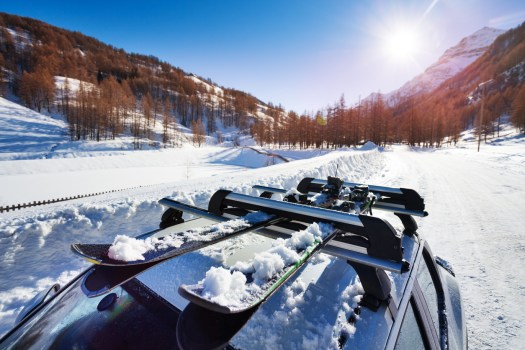 Beautiful view of sunny snowcapped mountains with skis fastened on car roof rails in the foreground. Photo: ICarhireinsurance.com. Skiers Over New Year Prepare for a £450 Wipeout at the Car Hire Rental Desk.