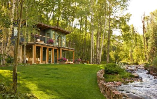 The exterior of the house. Book your stay at this riverfront house in Aspen here. Aspen Snowmass is opening for the Summer Season.
