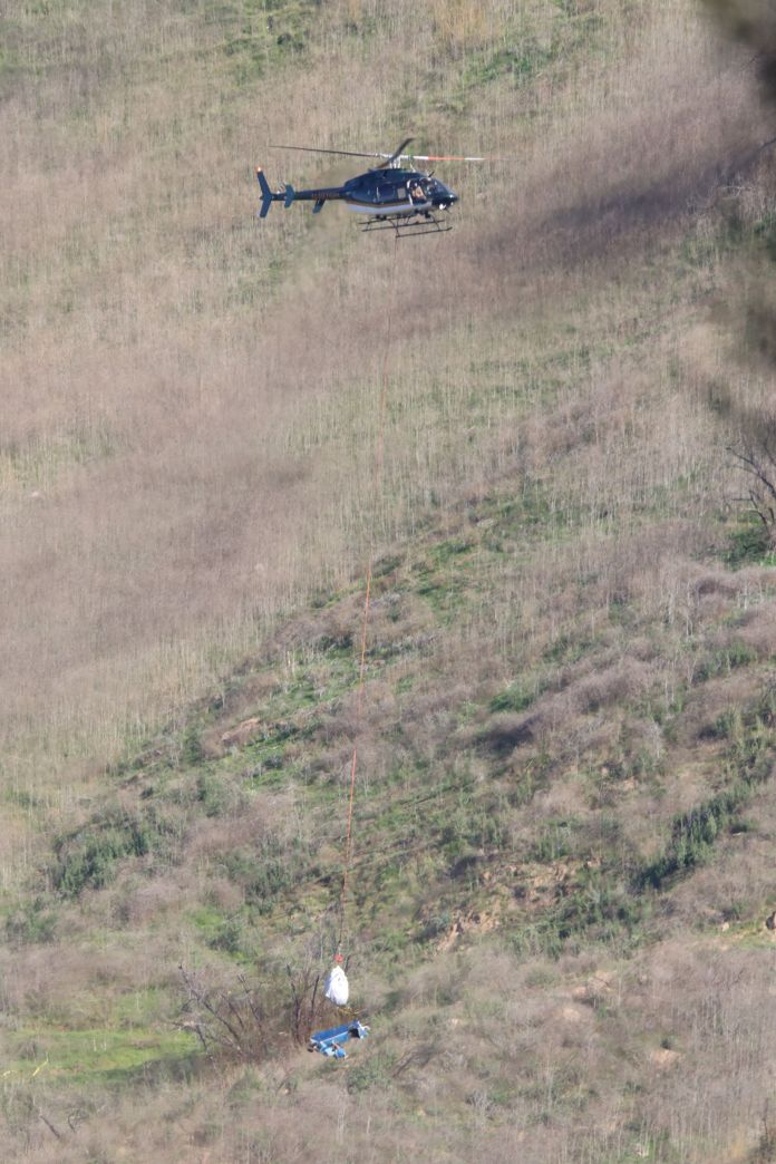 Helicopter transports debris away from accident site