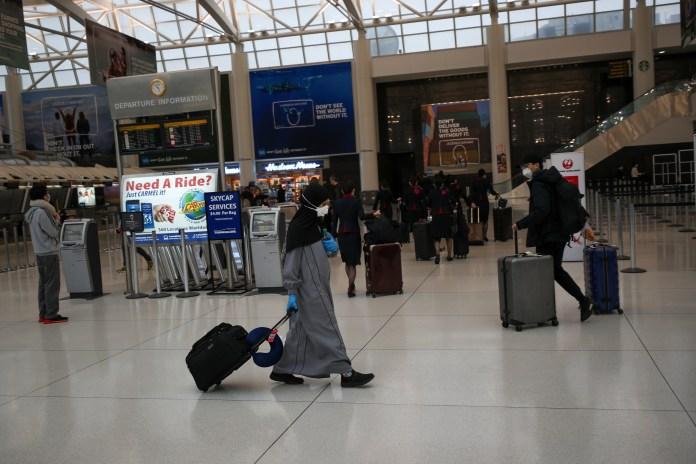 People wear masks at New York JFK Airport