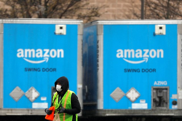 An Amazon worker in a face mask walks by trucks parked at an Amazon facility as the global coronavirus outbreak continued in Bethpage on Long Island in New York