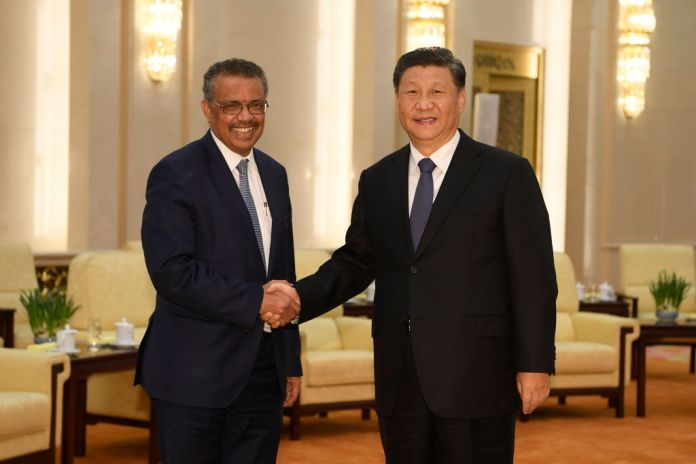 WHO Director-General Tedros Adhanom shakes hands with Jinping