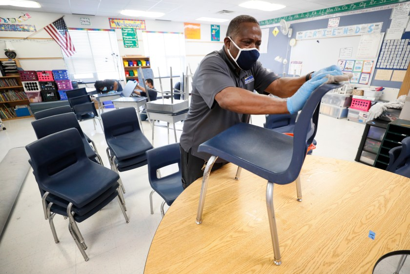 A custodian cleans chairs in a classroom