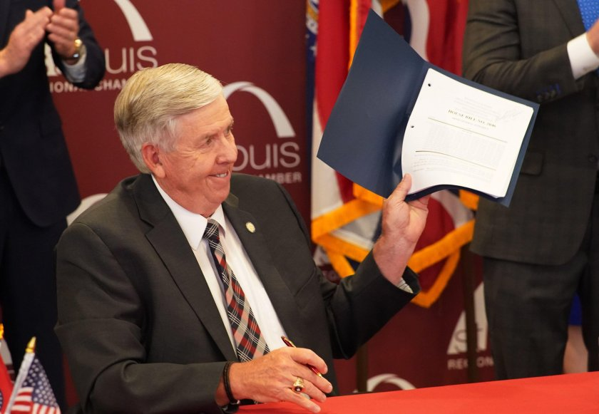 Missouri Governor Mike Parson displays a signed copy of HB 2046 expanding license reciprocity provisions in the state of Missouri on July 10