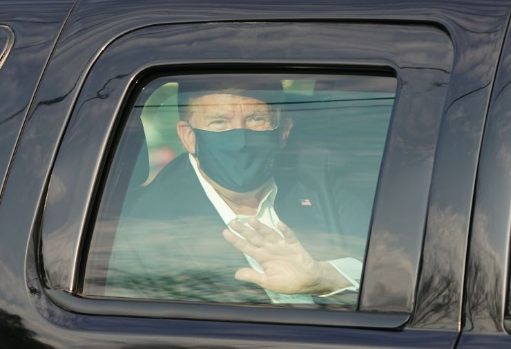 Donald Trump waves at supporters gathered outside as he battles coronavirus