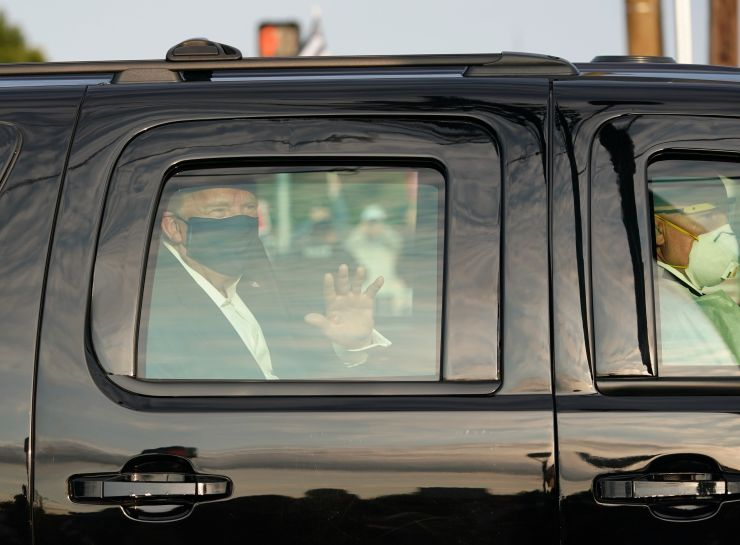 The president was pictured wearing a mask with the windows up as he waved to supporters