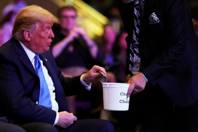 Donald Trump donates money as he attends a service at the International Church of Las Vegas