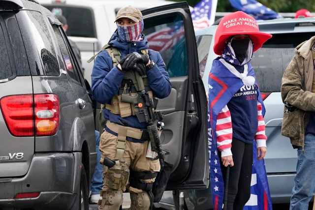 One supporter of President Trump holds a gun as another a baseball bat