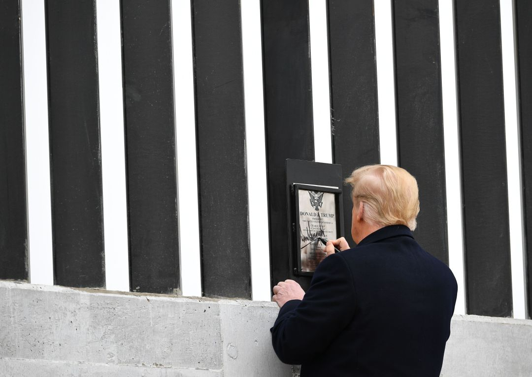 The president appeared to sign the wall before speaking