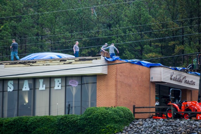 Workers put a canvas over a roof that was torn off in Pelham, Alabama