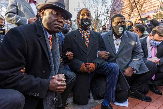 Attorney Ben Crump (L) and Rev. Al Sharpton, the founder and President of National Action Network,(C) and George Floyd's nephew kneel outside the Hennepin County Government Center on the opening day of the trial of former Minneapolis police officer Derek Chauvin