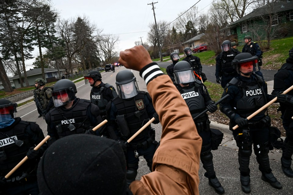 A black man raises his fist in the air as he yells at police donning riot gear