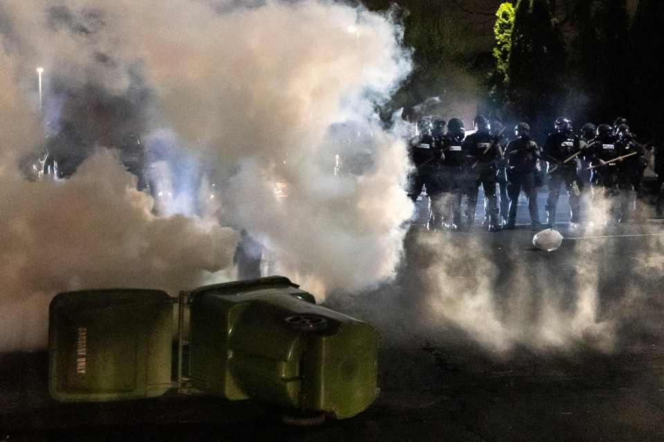 Police officers in riot gear fire tear gas in front of the Brooklyn Center Police Station