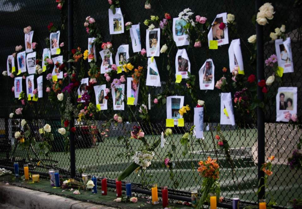 Photos of missing residents in makeshift memorial at the site of a collapsed building