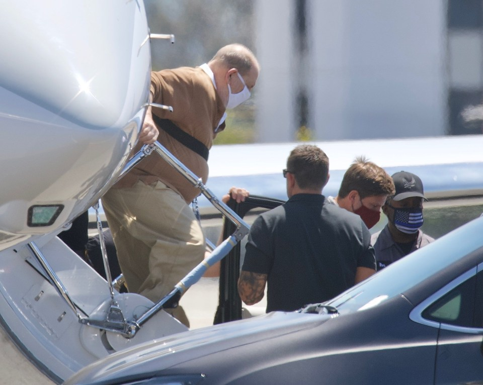 Weinstein was seen being held by a chest strap as he went down the steps of the jet