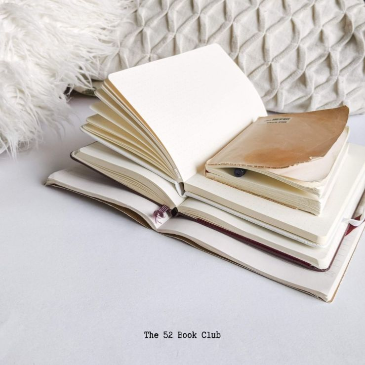 A stack of opened, blank journals on a white background.