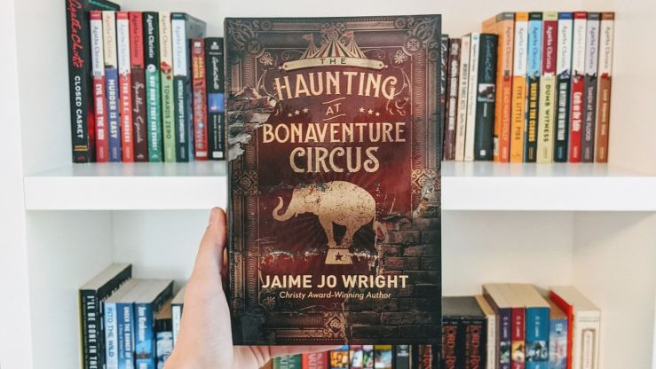 The Haunting at Bonaventure Circus book cover in front of white bookshelf filled with books