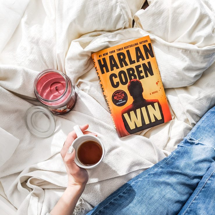 Win by Harlan Coben book on white blankets. Girl holds mug of coffee.