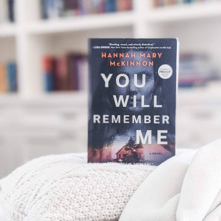 You Will Remember Me book by Hannah Mary McKinnon, set on top of a white pillow and blanket