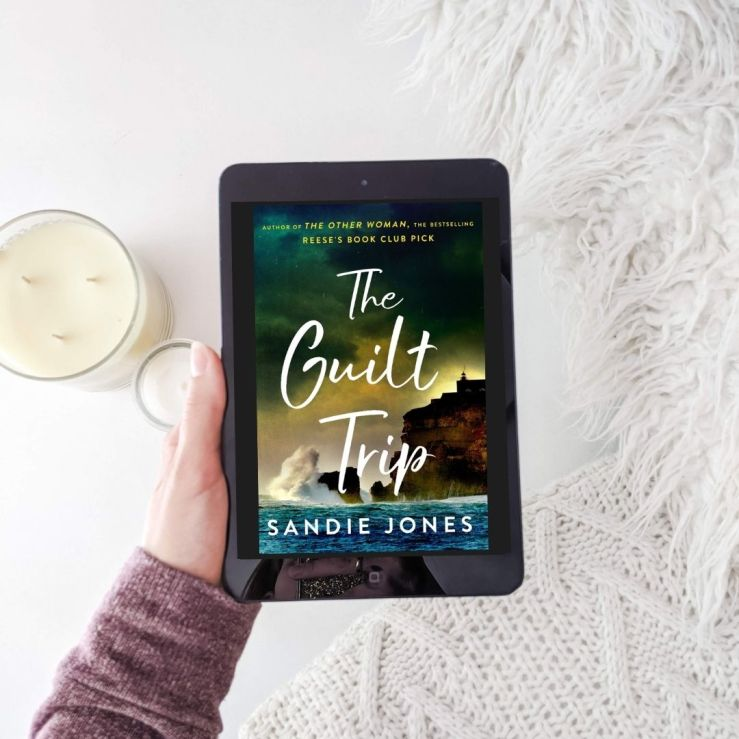 The Guilt Trip by Sandie Jones, book on e-reader set against white background with pillows and candles