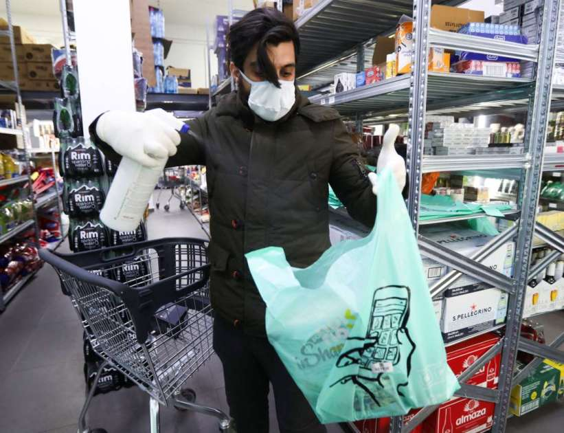 A worker sanitizing a bag of groceries during COVID-19 outbreak