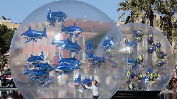 "A boy looks at fish-shaped balloons installed in a water fountain to mark April Fools' Day, called ""Poisson d'Avril"" in ..."