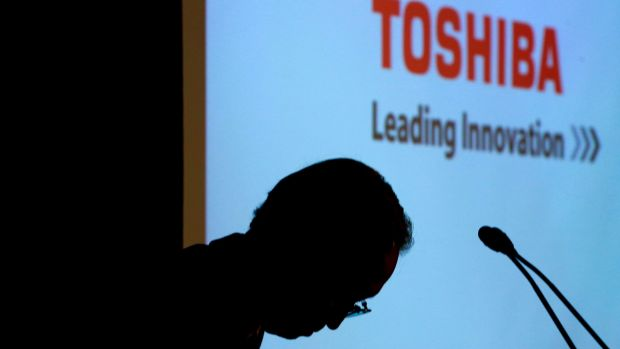 Toshiba chief executive Satoshi Tsunakawa bows during a news conference at the company's Tokyo headquarters in which he ...