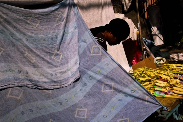A palaspas vendor peeks out from a makeshift tent on a sidewalk just outside the Holy Cross Parish in Makati City. Photo by: Chris Quintana