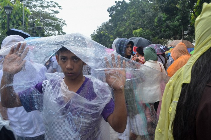 A man uses a plastic cover as raincoat during Pope Francis's mass in Luneta. Photo by: Bart Manoguid