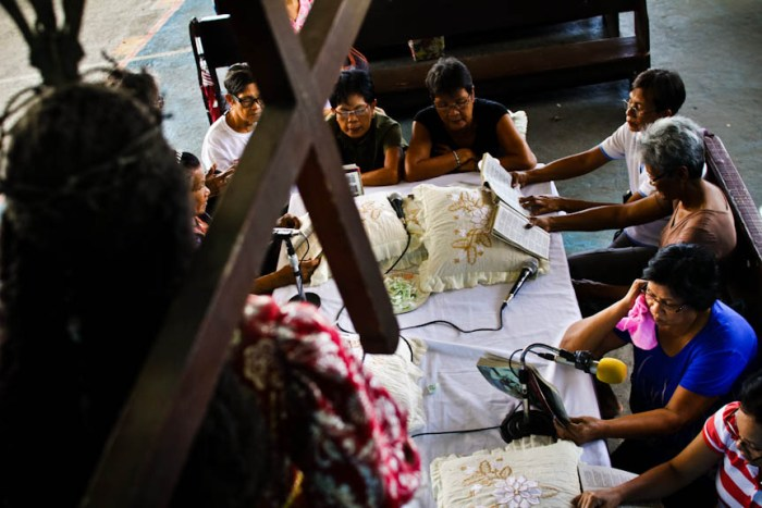 An image of the Black Nazarene is on stage in front of the table where elder women sing the Pabasa on Maundy Thursday in the village of San Antonio in Bay, Laguna. Photo by: Chris Quintana