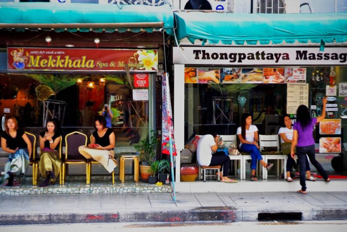 Women waiting for customers in front of spas in Bangkok, Thailand. Photo by: Sonny Yabao