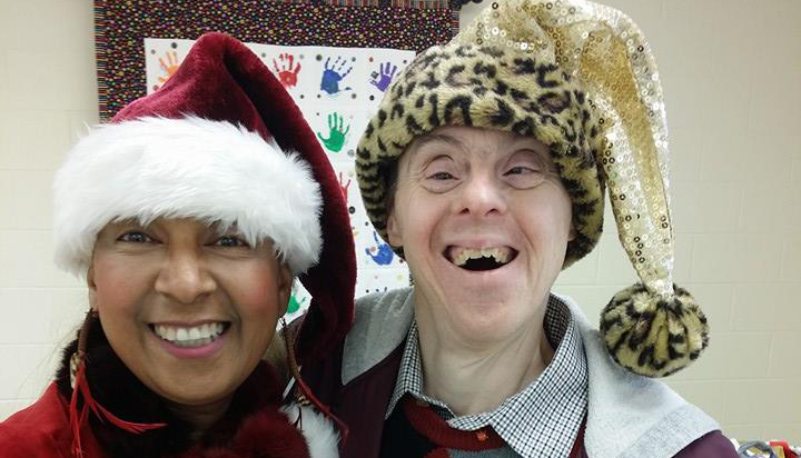 Friends wearing Christmas hats smile for the camera at the Christmas Cookie Party