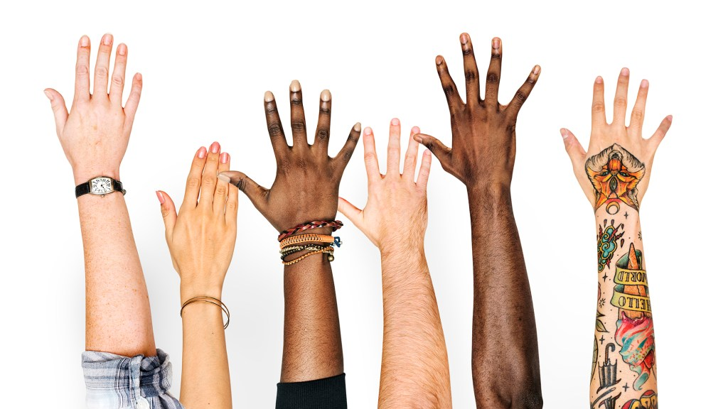 A diverse group of hands raised to show interest in helping.