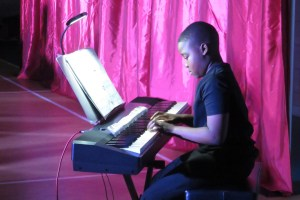 A photo of one of our piano students playing in our end of year show.