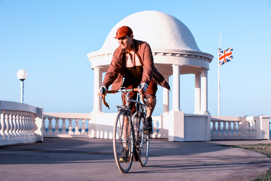 Journeys from My Doorstep  - A cyclist pedals towards the camera with a union jack fluttering behind him and the white domes of the King George V Colonnade