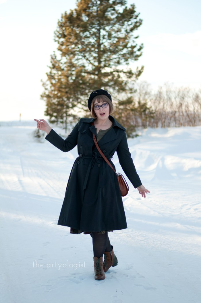a lady wearing a black vintage style trench coat, satchel and beret