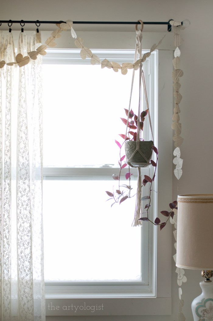 a heart garland made of book pages draped across a window with lace curtains and a hanging plant