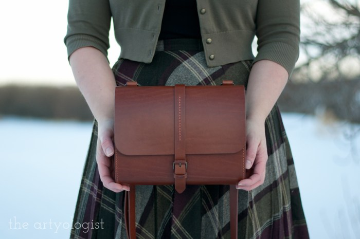 holding a vintage style satchel purse in copper coloured leather